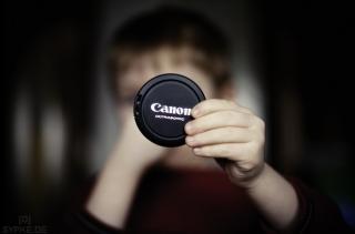 Kind hält Canon Objektivdeckel